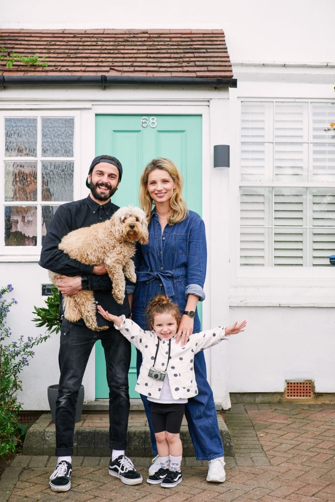 Family with their dog stood in front of their front door in East London
