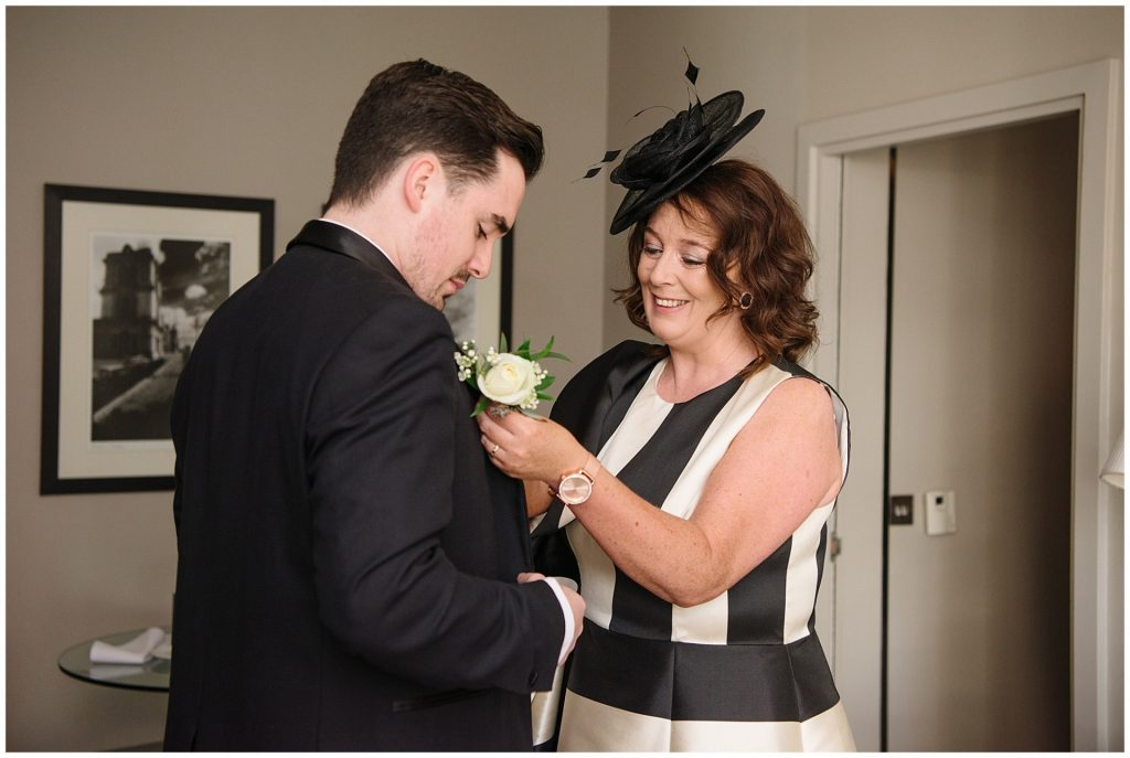 grooms mum helping him put on his flower buttonhole in hotel room