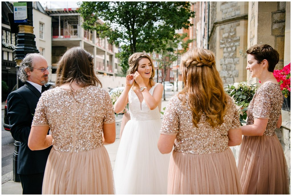 bride putting in earnings whilst stood outside of Farm Street Church in Mayfair with her Bridesmaids