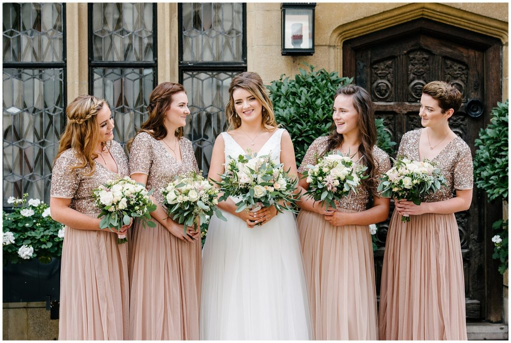 Bride stood laughing with her bridesmaids all wearing peach sequinned dresses in Mayfair