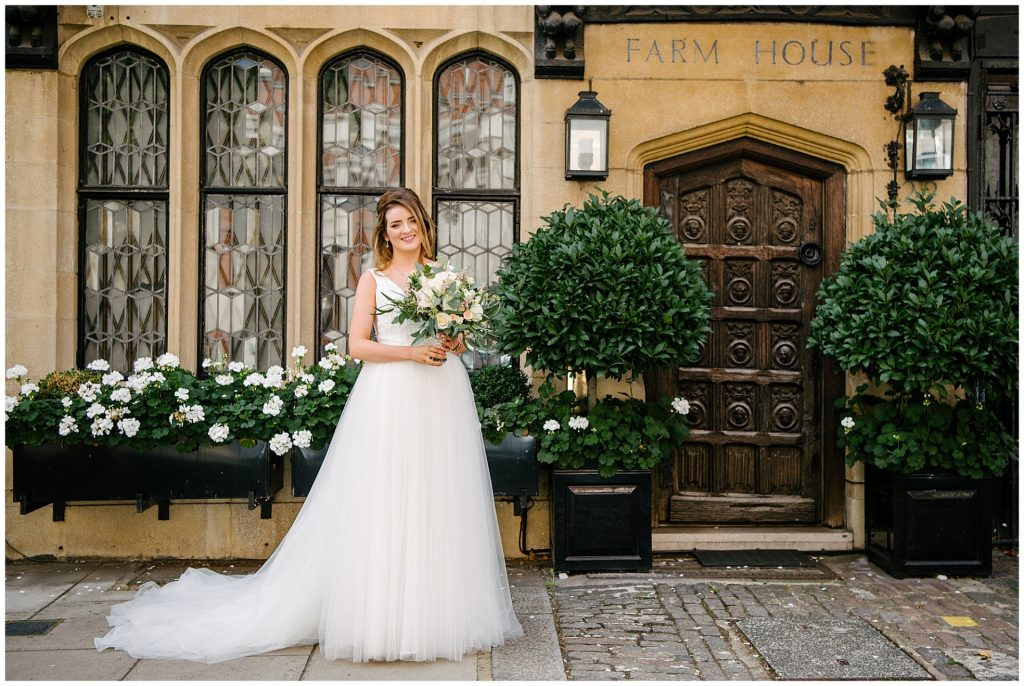 Bride stood smiling outside of Farm Street Church on Summer Wedding Day
