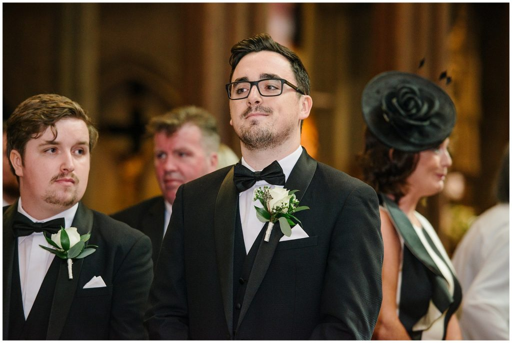 Groom stood at the alter on his wedding day at Farm Street Church in Mayfair
