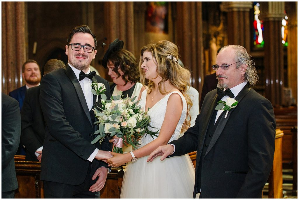 Groom crying whilst meeting his bride during wedding ceremony at Farm Street Church in Mayfair