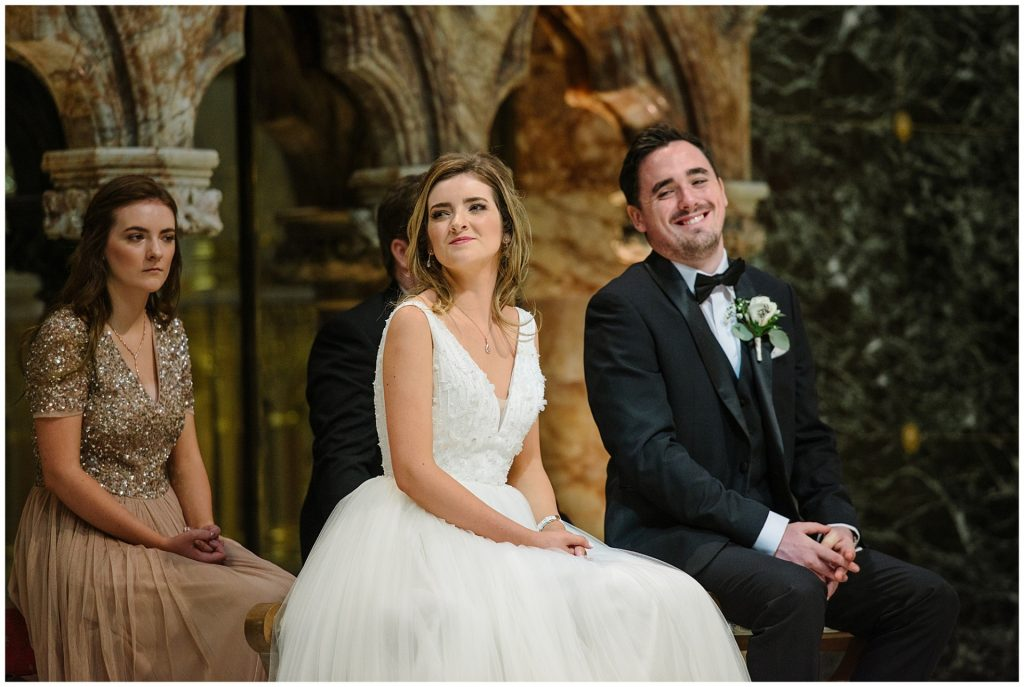 bride and groom sat down smiling during wedding ceremony at Farm Street Church