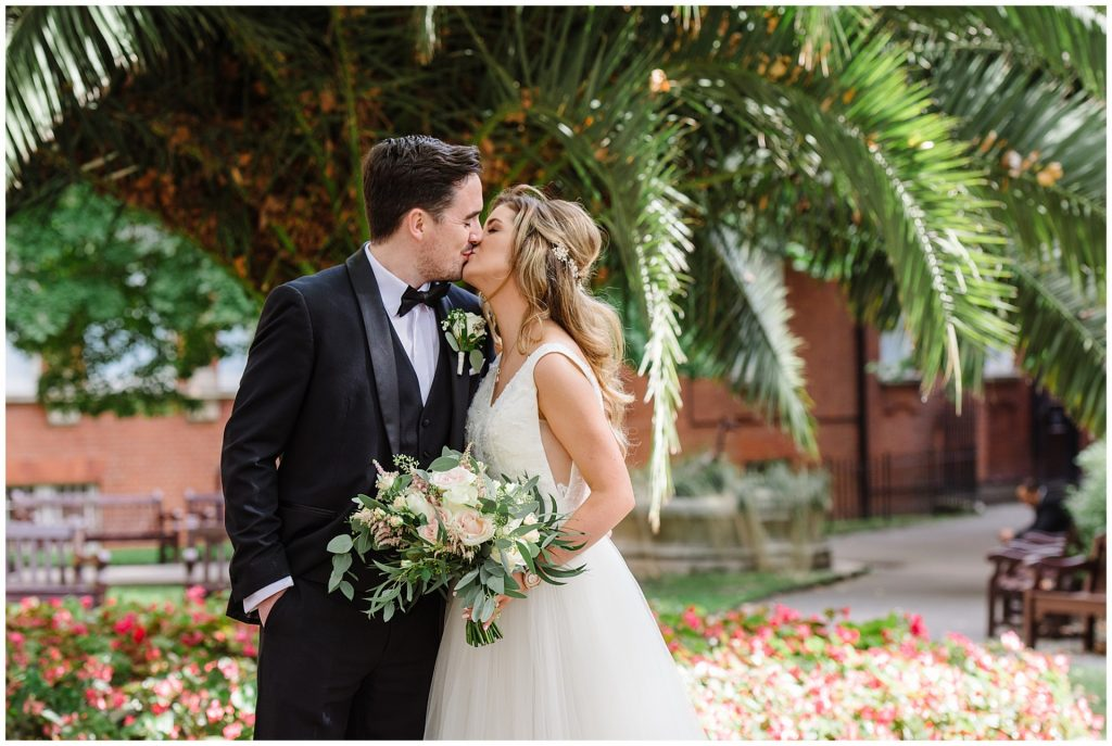 Bride and groom kissing in front of a tropical plant in Mount Street Gardens