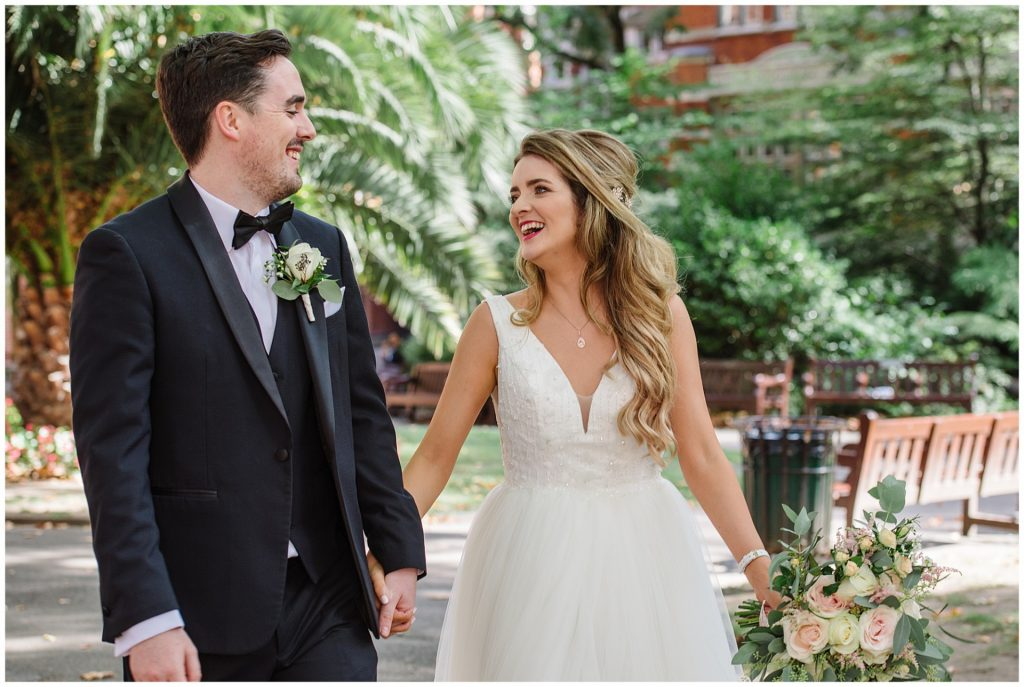 bride and groom laughing in mount street gardens during summer wedding in Mayfair
