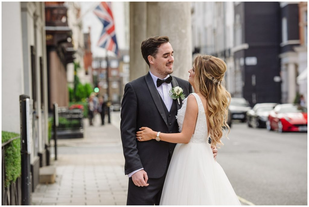 Happy bride and groom on a london street during summer wedding in Mayfair