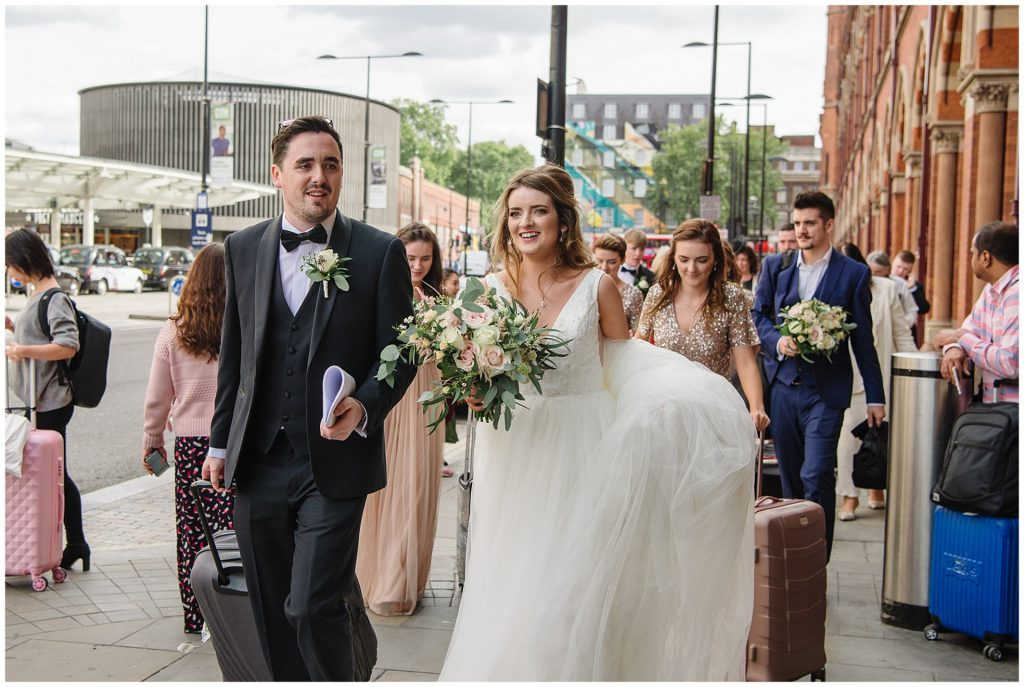 bride and groom walking with suitcases outside St Pancras during summer wedding