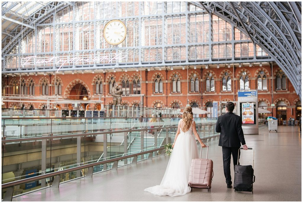 bride and groom walking away with suitcases at St Pancras