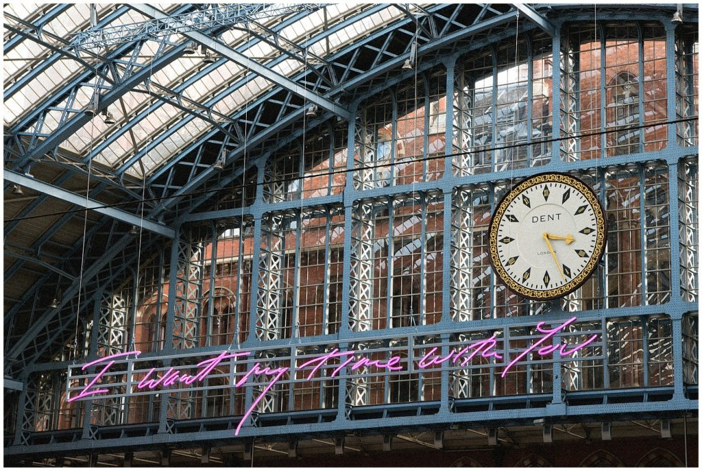 neon writing and clock face at St Pancras Station in London