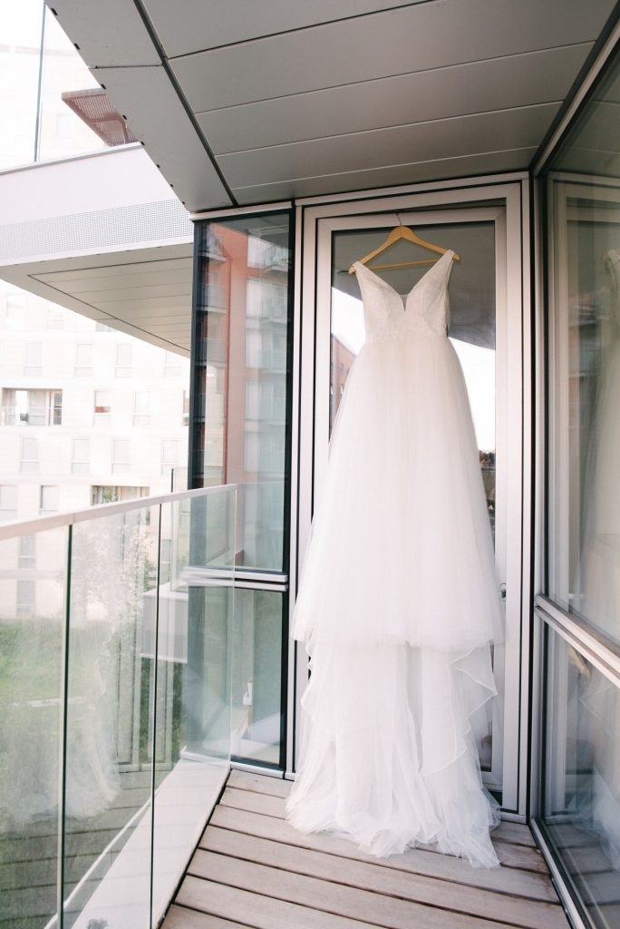 White wedding dress hung on a london balcony during the summer