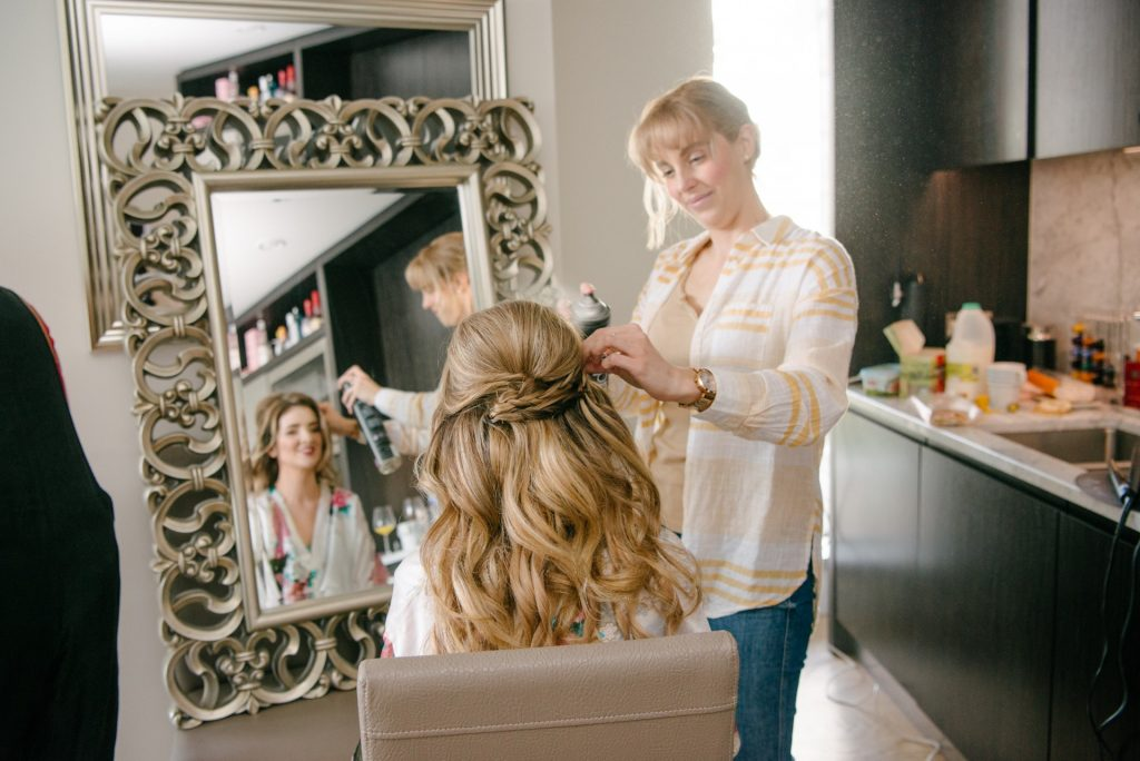 Bride looking into mirror whilst having her hair done on summer wedding day