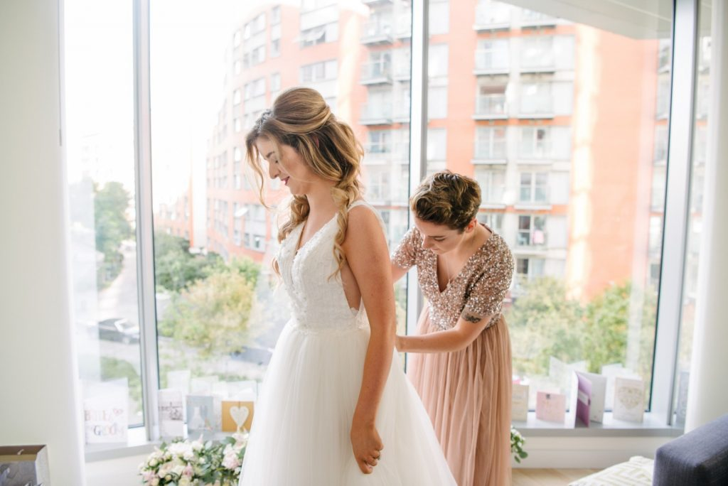 bridesmaid wearing pink helping to do up brides wedding dress