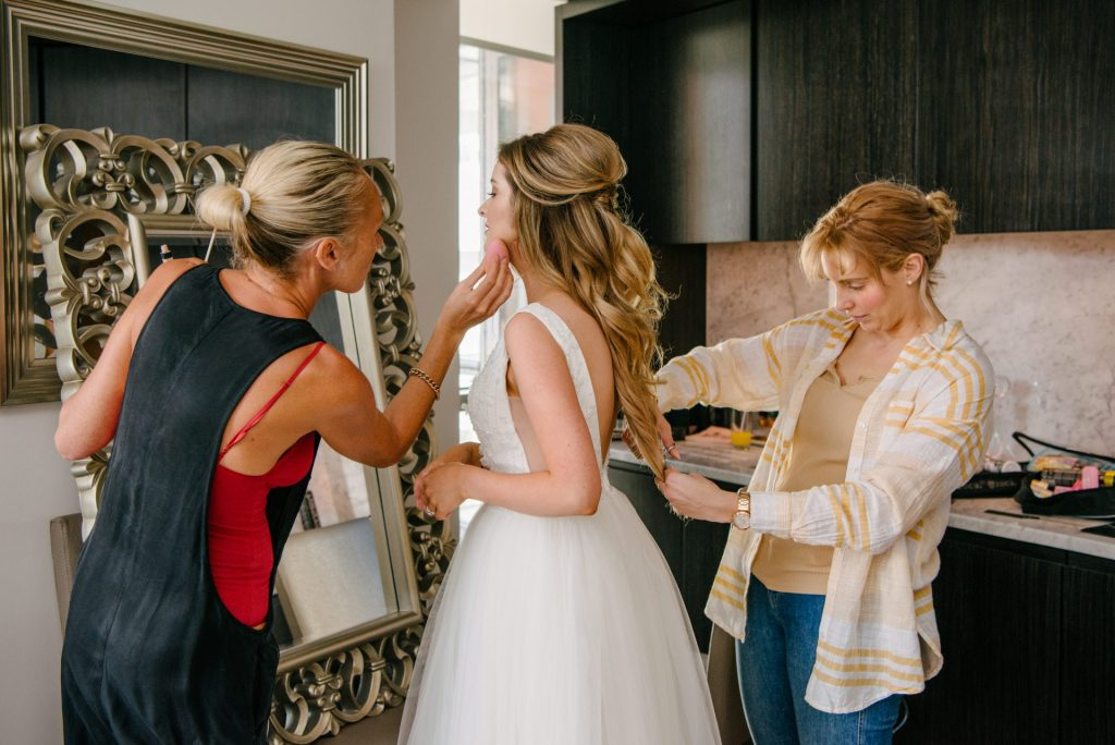 Bride having her hair styled and makeup applied at the same time