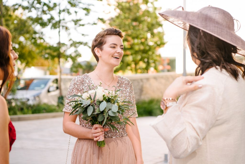bridesmaid laughing whilst wearing pink glitter dress and holding flowers