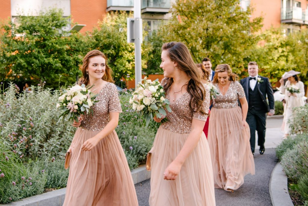 bridesmaid walking and laughing whilst wearing pink sequinned dresses
