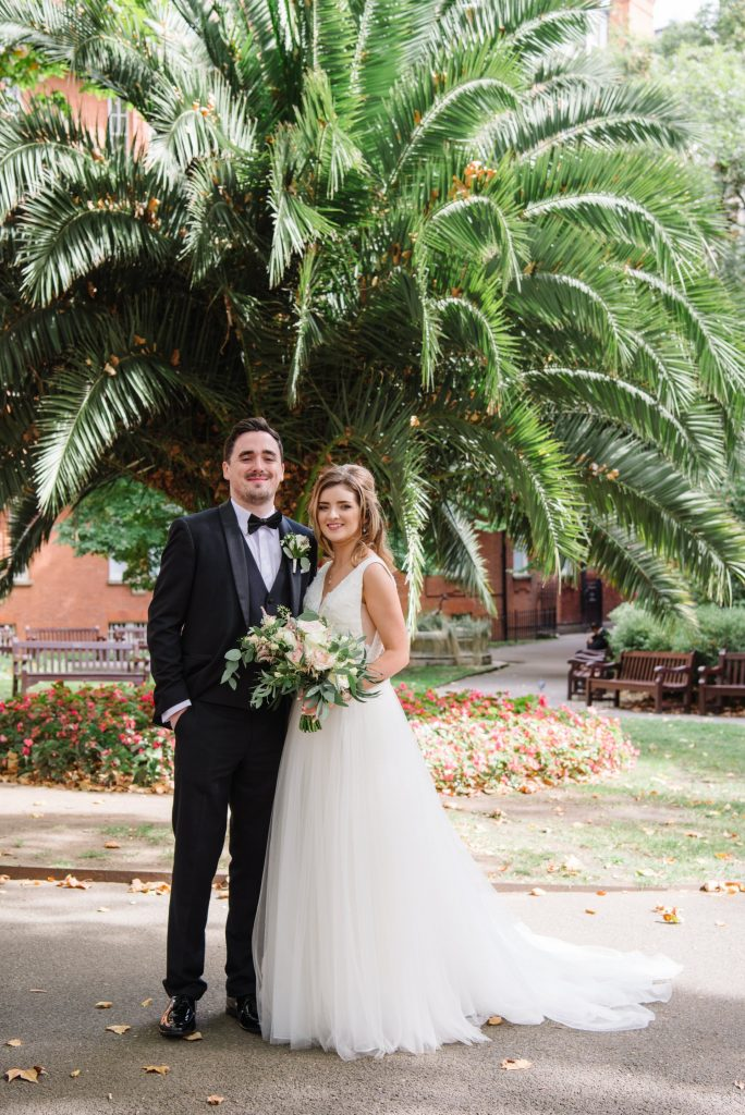 happy bride and groom in front of a tropical plant in Mount Street Gardens