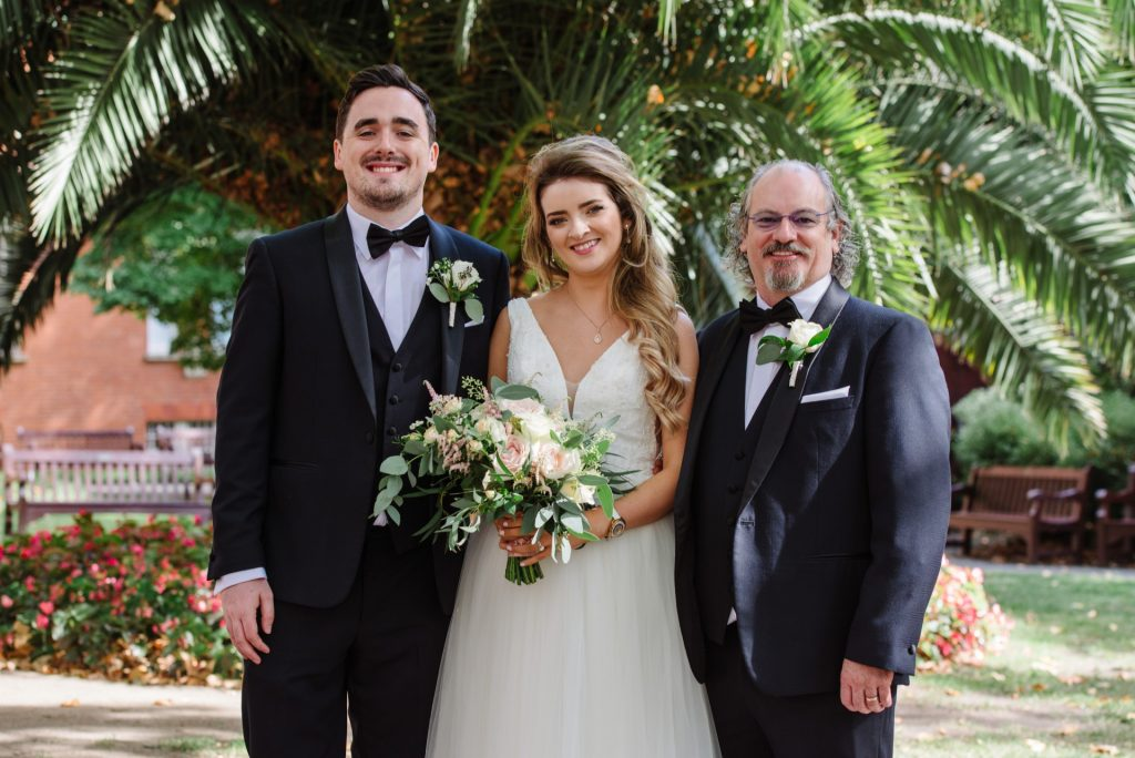 bride and groom with father in mount street gardens during summer wedding in Mayfair