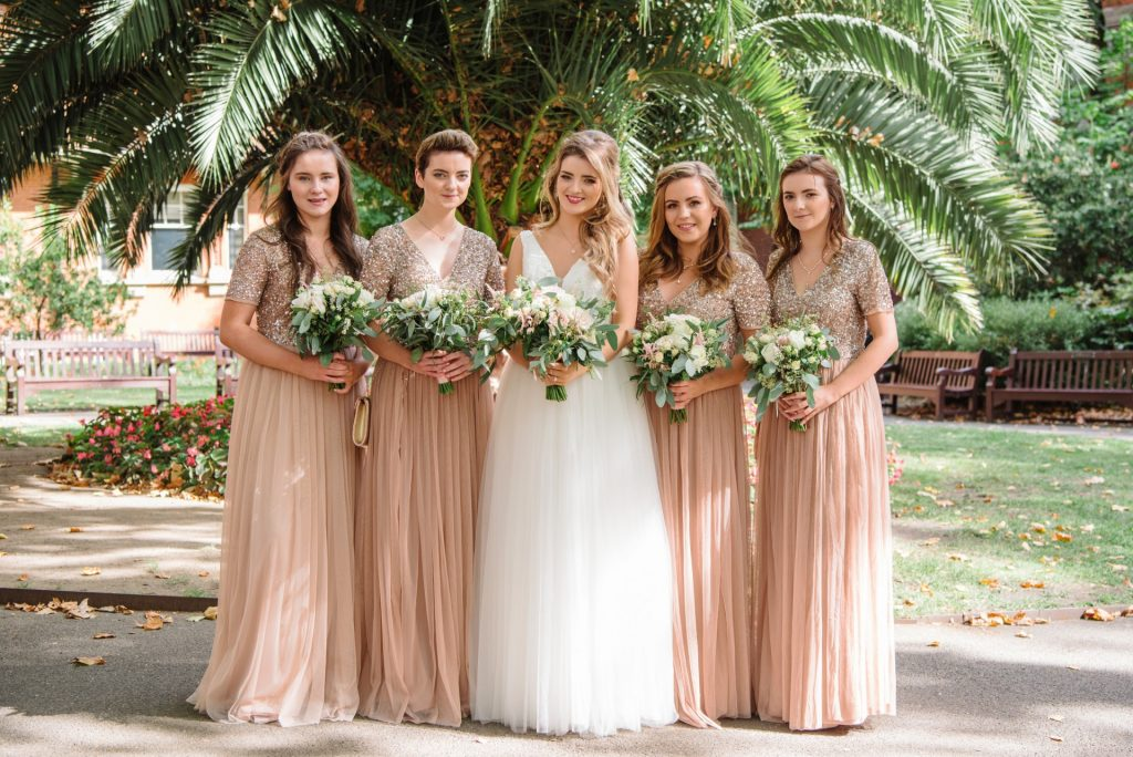 bride with her bridesmaids in mount street gardens during summer wedding in Mayfair