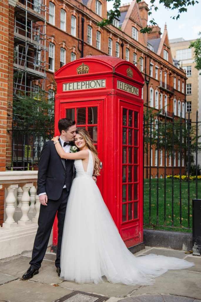 bride and groom in front of red telephone box during summer wedding in Mayfair