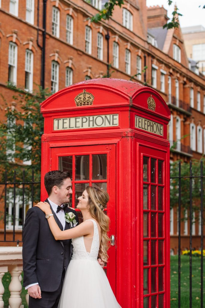 happy bride and groom in front of red telephone box during summer wedding in Mayfair