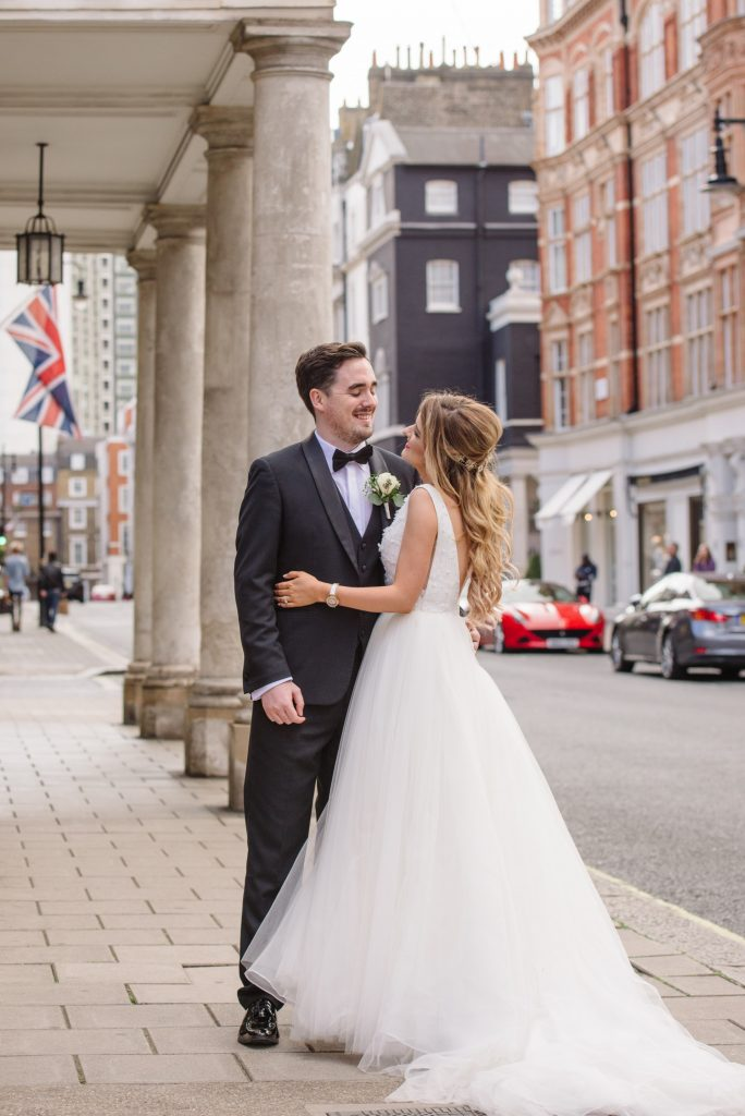 bride and groom laughing on a london street during summer wedding in Mayfair