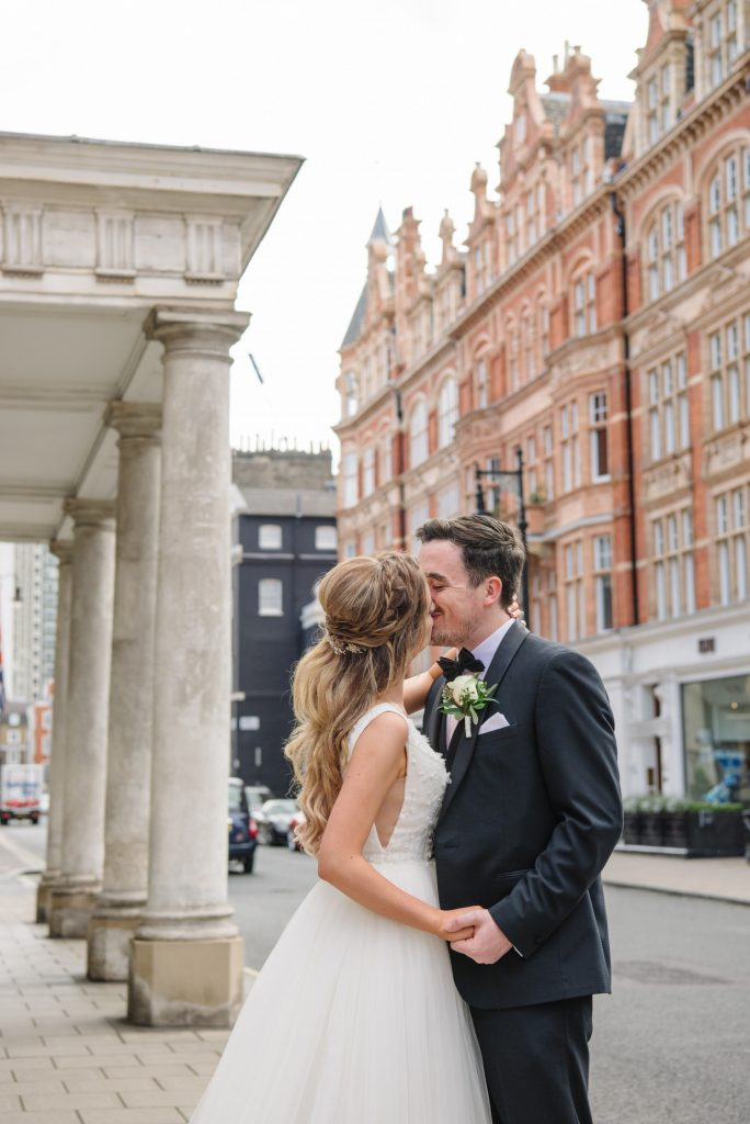 bride and groom kissing on a london street during summer wedding in Mayfair