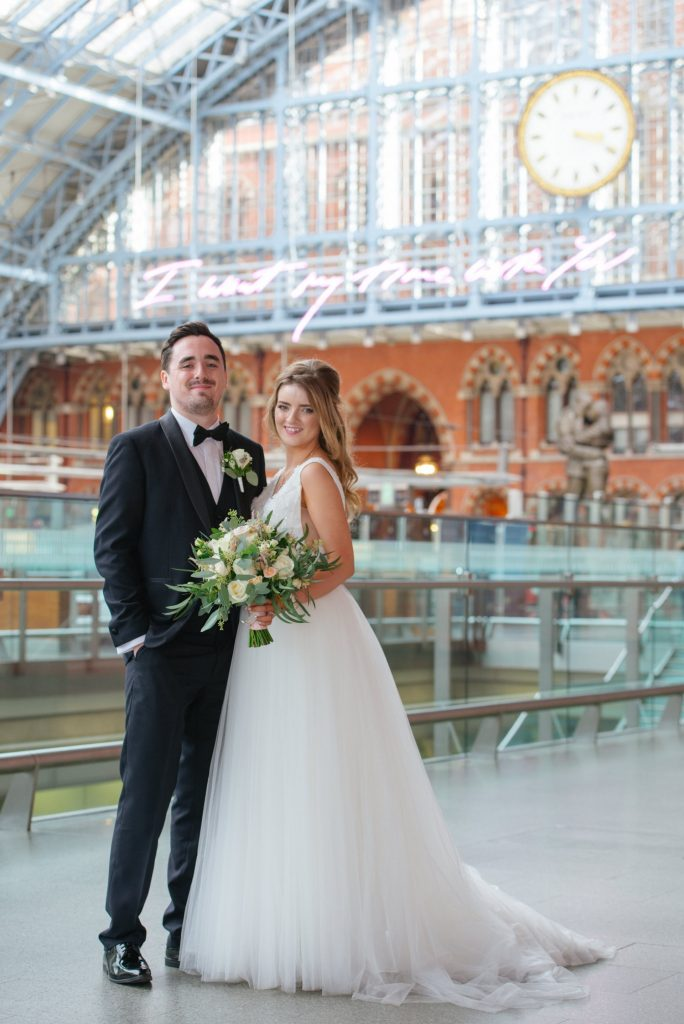 bride and groom in front of the clock at St Pancras Eurostar station