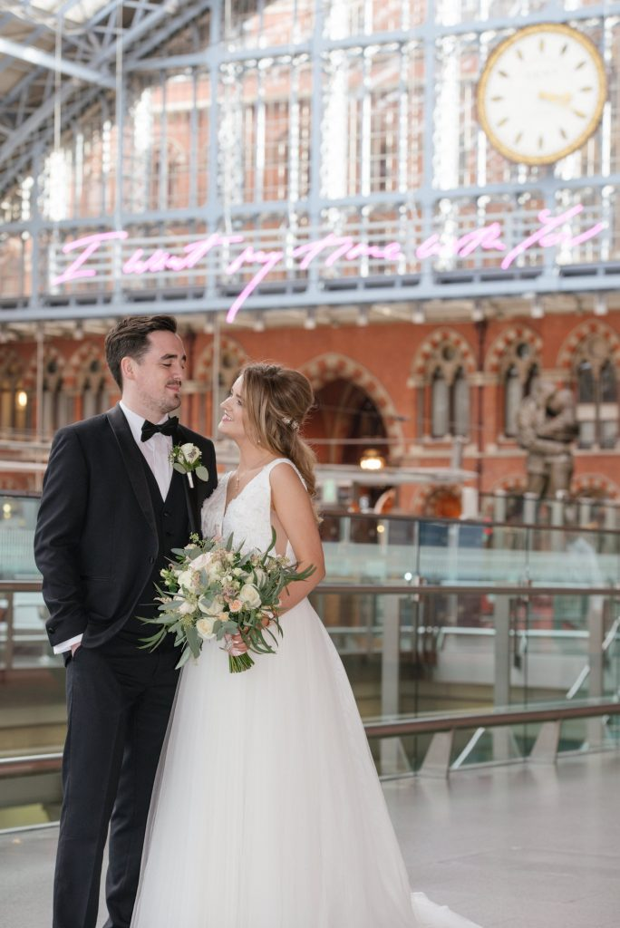 bride and groom smiling in front of the clock at St Pancras Eurostar station