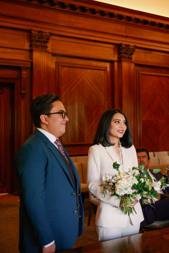 Bride and groom stood smiling during their intimate wedding ceremony at Marylebone Town Hall