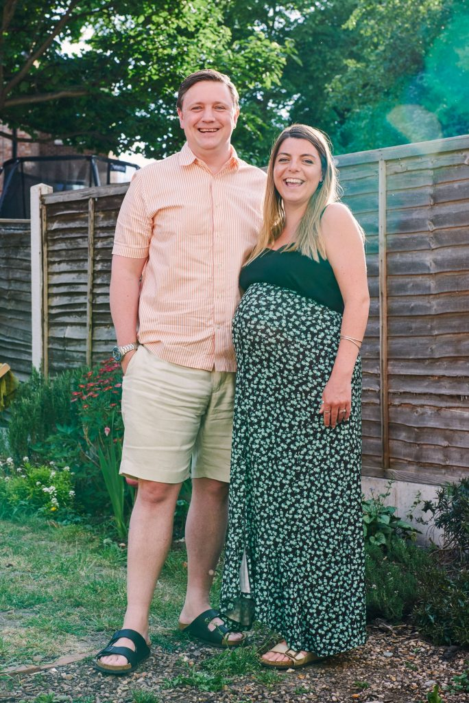 Pregnant women stood with her husband in their Garden in Leyton