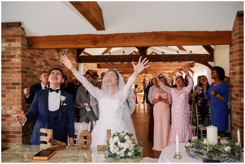 bride, groom and wedding party signing during a wedding ceremony at Long Furlong Barn