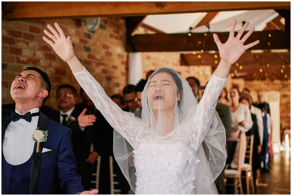 bride with her arms in the air signing gospel hymns during a wedding ceremony