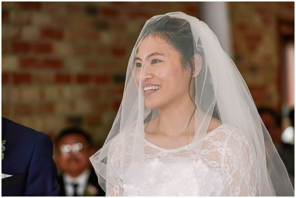 bride smiling during rustic wedding ceremony at Long Furlong Barn