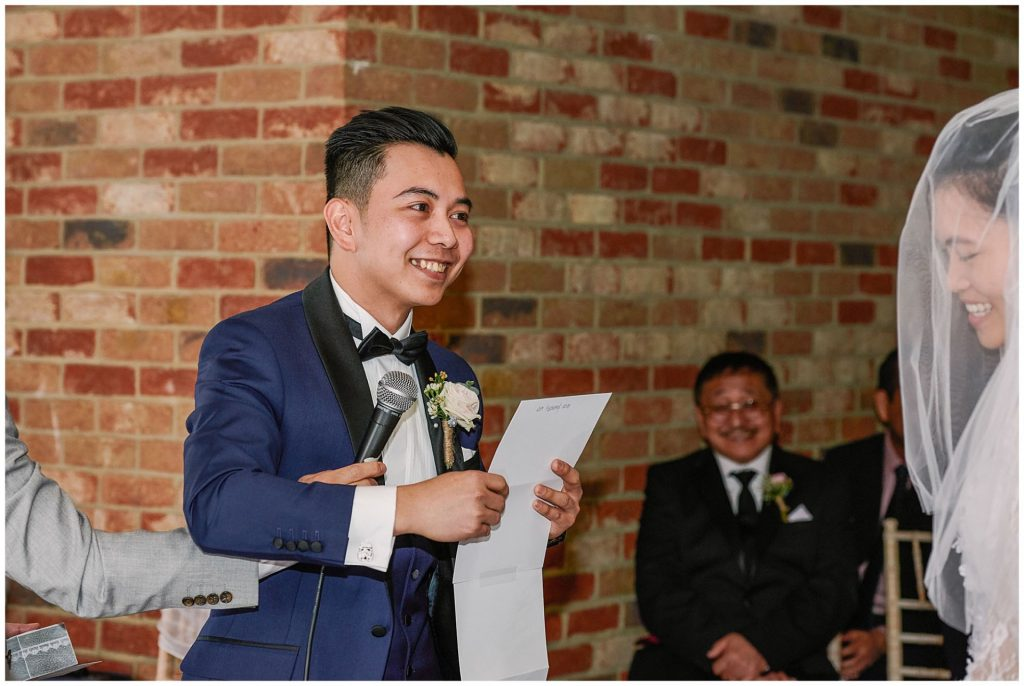 Groom reading personalised wedding vows to his bride at Long Furlong Barn