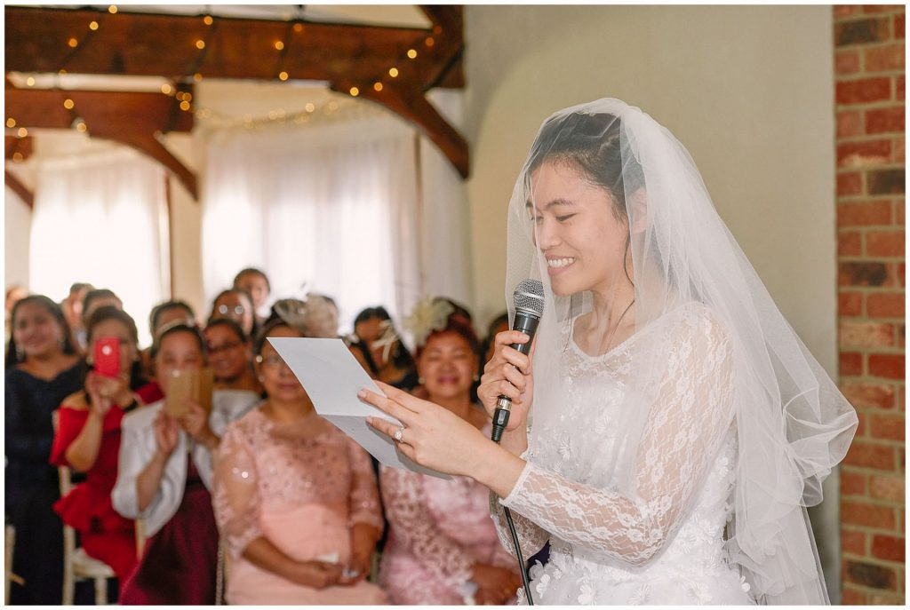 Bride reading personalised vows during wedding ceremony at Long Furlong Barn