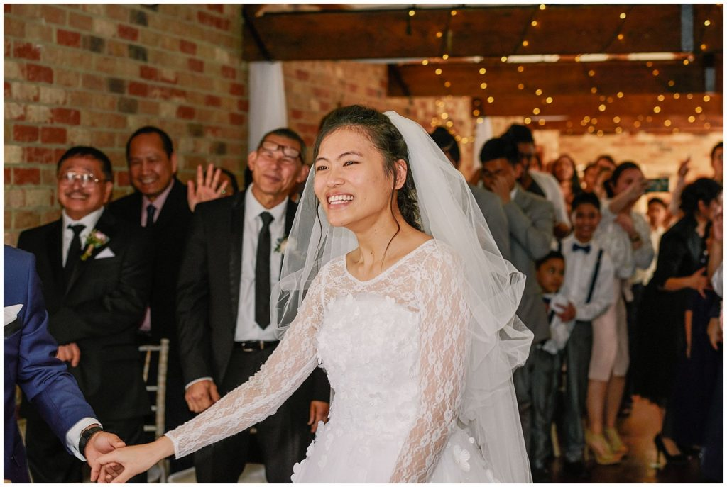Bride smiling during rustic winter barn wedding ceremony