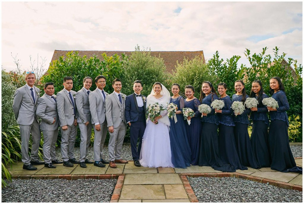 Bride and groom stood in a line with with bridal party in a garden