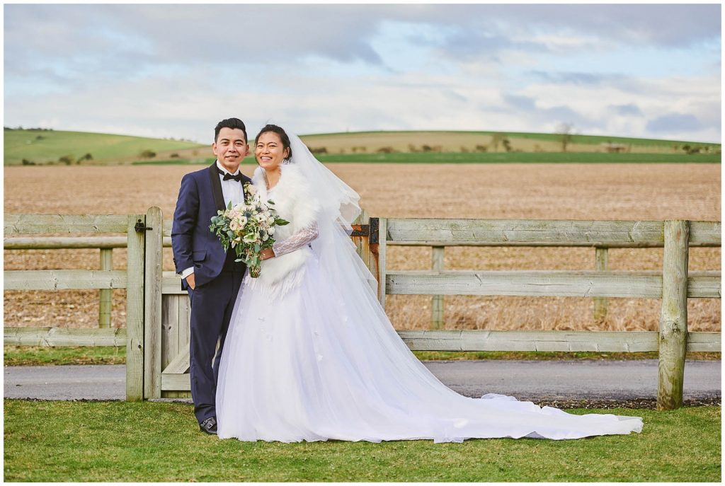 bride and groom smiling in a field during rustic winter wedding at Long Furlong Barn