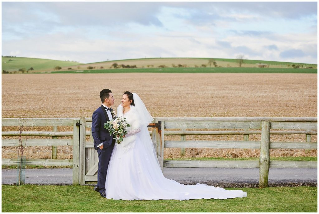 bride and groom smiling in a field during rustic winter barn wedding