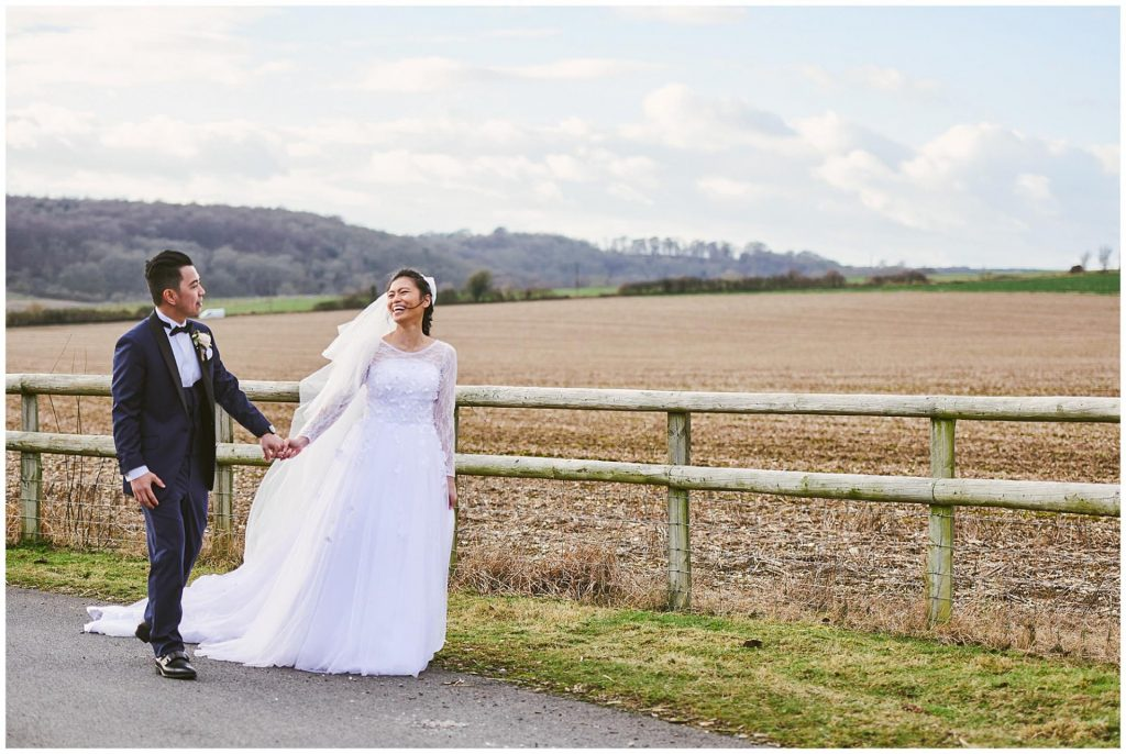 bride and groom walking next to a field during rustic winter barn wedding