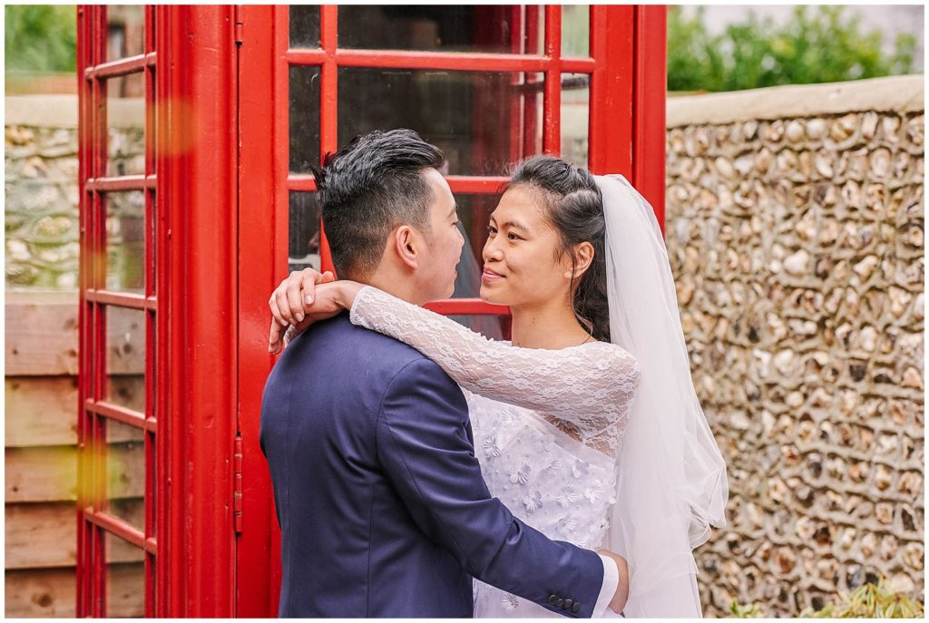 bride and groom smiling with arms around each other in front of red telephone box