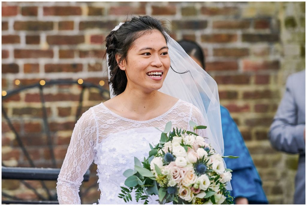 Bride smiling during rustic winter barn wedding