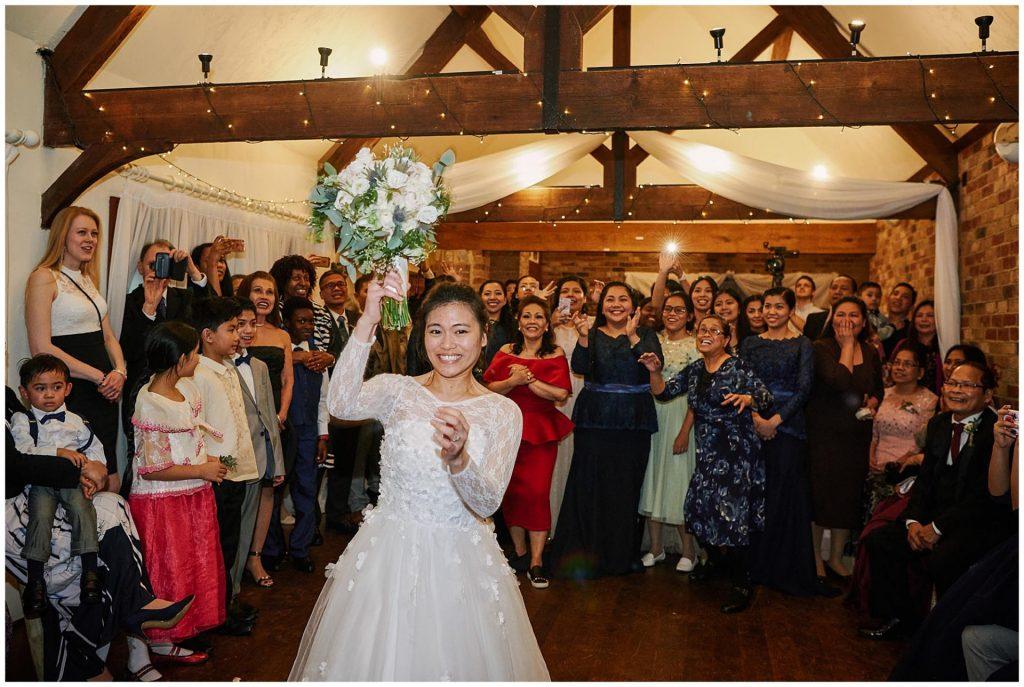 Bride throwing her flower bouquet during winter barn wedding
