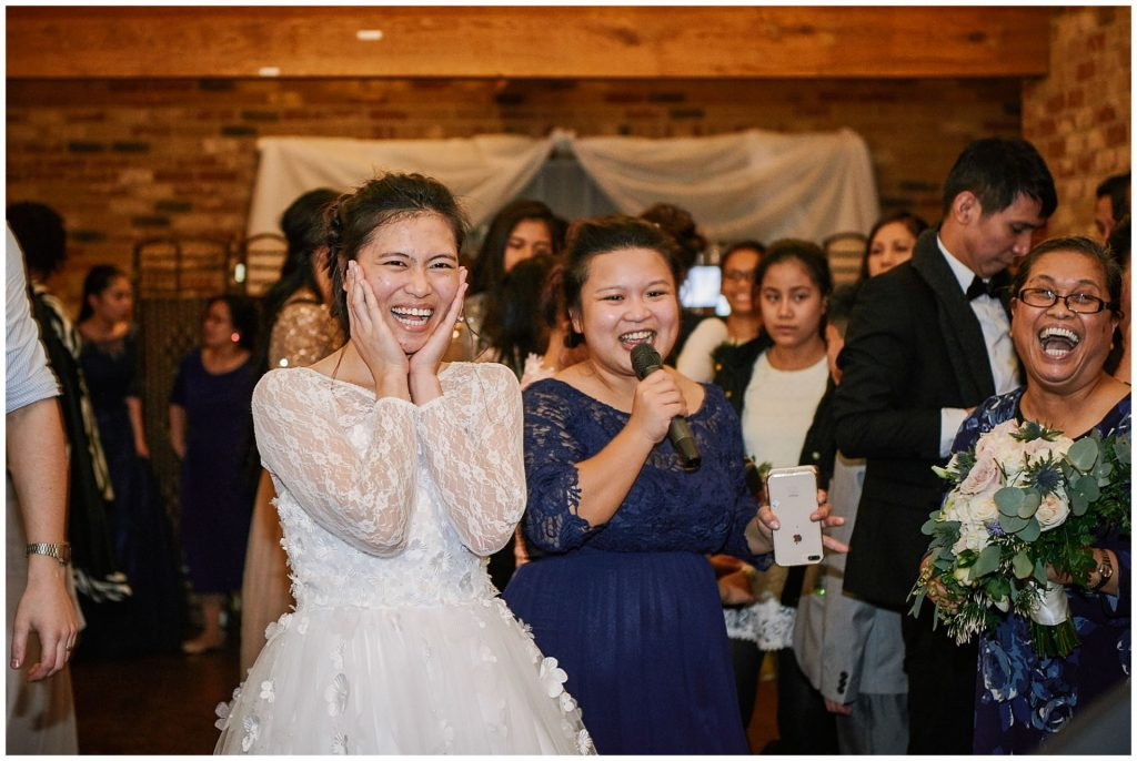 Bride laughing during rustic barn winter wedding reception