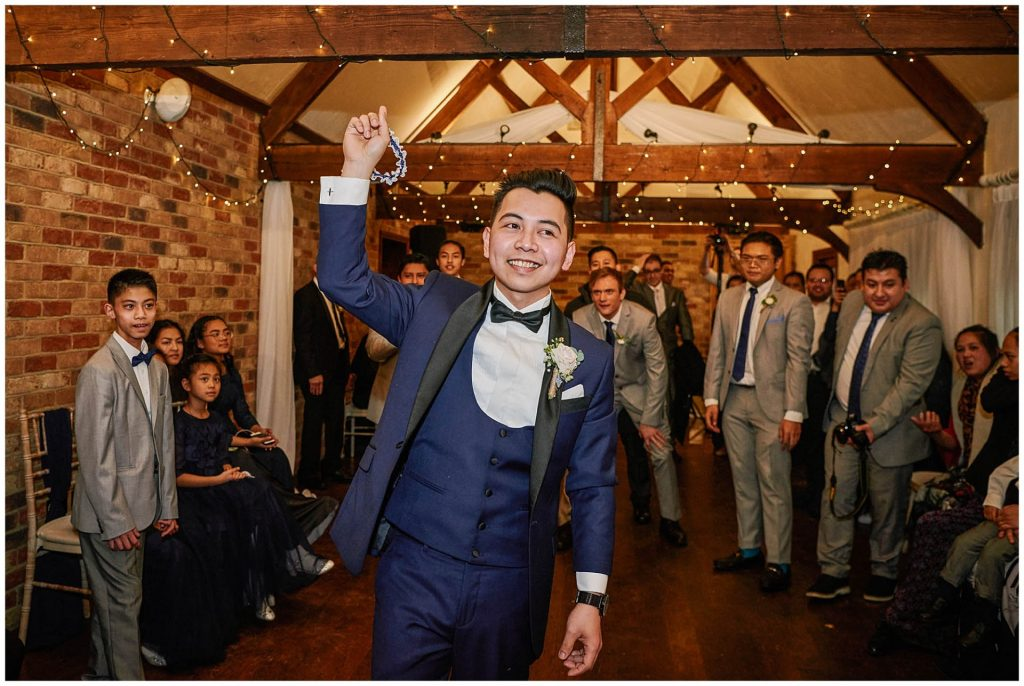 Groom throwing the garter during rustic barn  wedding reception