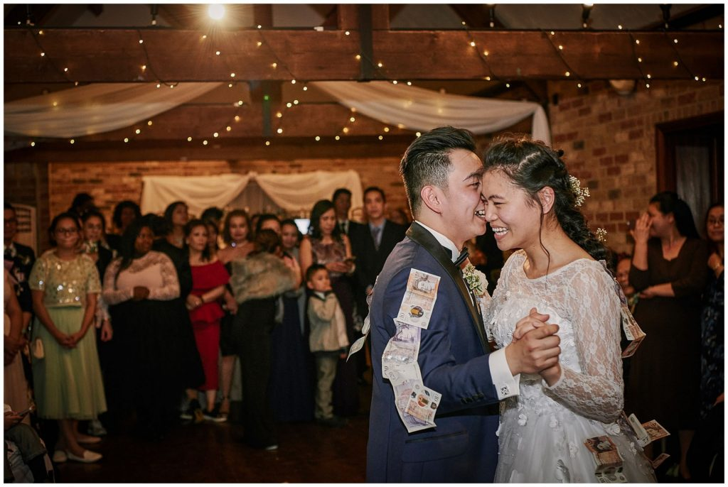 Bride and groom laughing during filipino money dance at winter barn wedding