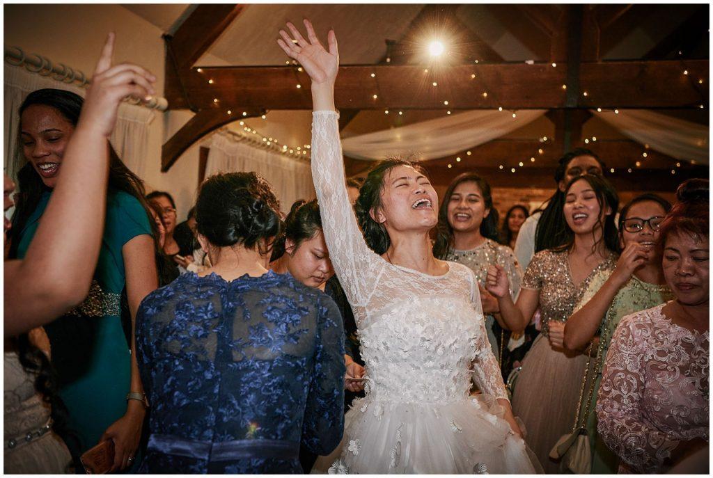 Bride dancing and singing during winter wedding reception at Long Furlong Barn