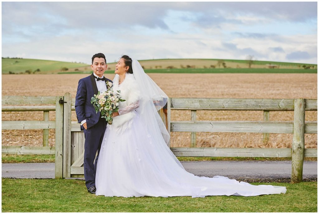 bride and groom laughing in a field during winter wedding at Long Furlong Barn