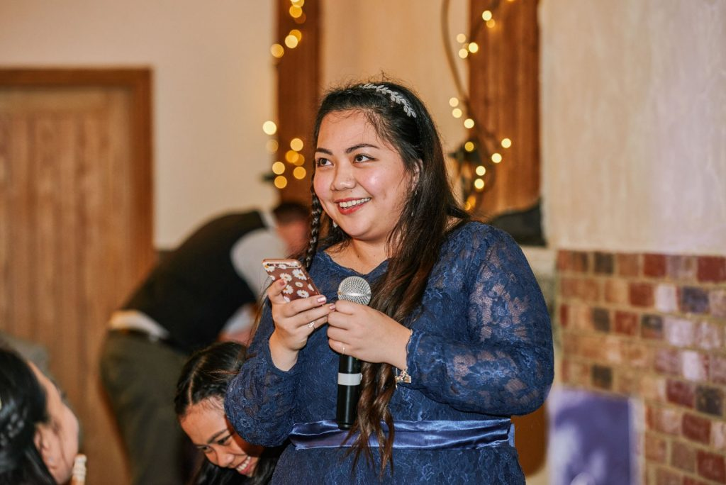 Bridesmaid giving a speech during a winter barn wedding with fairy lights behind